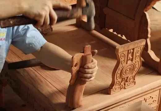 家具组装组装在行业里叫攒活儿,就是利用榫卯结构将雕刻好的部件,组装成成品家具。因为红木家具自重很大,如果组装时放在不平的地面上,腿上的受力不匀,容易造成家具的变形,一旦家具攒装完成后,就很难再矫正过来。所以木工师傅在攒活时,都会在水平、干净的地面上进行,好能及时判别家具成品是否装正。 6、红木刮磨工序